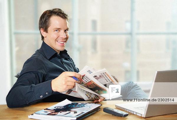 Fröhliches Sitzen am Schreibtisch beim Zeitungslesen