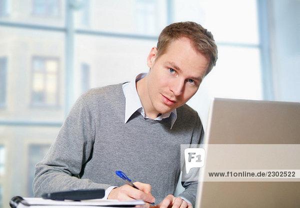 Mann sitzt hinter dem Computer und schreibt