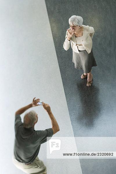 Mann hält Digitalkamera hoch  Frau bläst einen Kuss  von oben gesehen