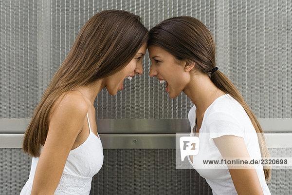 Teenager Zwillingsschwestern lehnen sich mit den Stirnen an  beide schreien  Seitenansicht