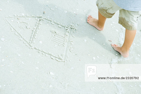 Child at the beach  standing next to drawing of house in sand  cropped view