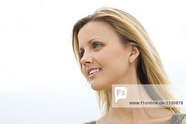 Blonde Frau lächelnd  wegschauend  Nahaufnahme