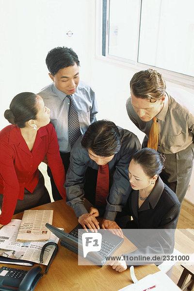 Gruppe von Fachleuten  die zusammen auf den Laptop schauen  Blick in den hohen Winkel