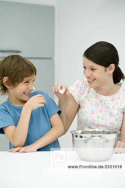 Bruder und Schwester stehen in Küche, Mädchen setzen gepeitschte Creme auf boy's Nase, beide lächelnd