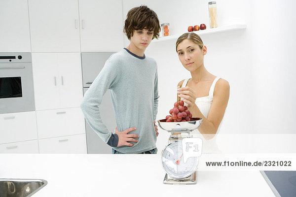 Mutter und Sohn stehen in der Küche  wiegen Trauben auf der Waage  Frau schaut in die Kamera