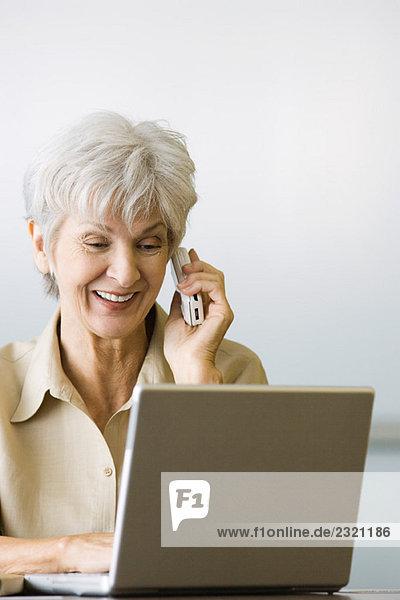 Seniorin mit Laptop und Handy  lächelnd  herabblickend