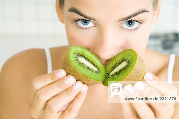Junge Frau riecht frisch geschnittene Kiwi  schaut in die Kamera  Nahaufnahme