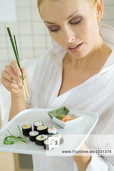 Frau hält Maki-Sushi und Essstäbchen und schaut nach unten.