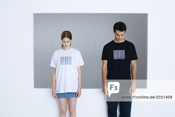 Two young adults wearing tee-shirts printed with bar codes  both looking down