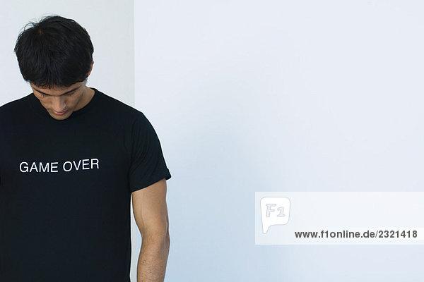 Der Mann trägt ein T-Shirt mit dem Aufdruck game over .
