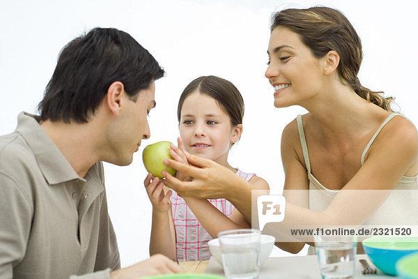 Familie der gesunden Esser  Mutter und Tochter halten den Apfel dem Vater entgegen.