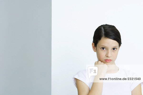 Preteen girl  hand under chin  looking at camera  portrait