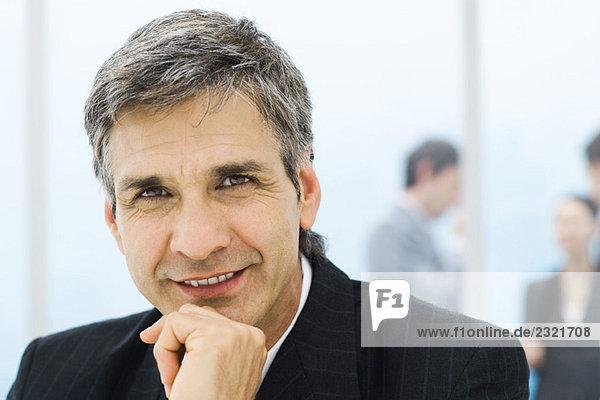 Geschäftsmann  Porträt  im Hintergrund stehende Kollegen