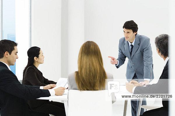 Geschäftsfreunde mit Besprechung  Manager auf den Tisch gelehnt  Zeigen