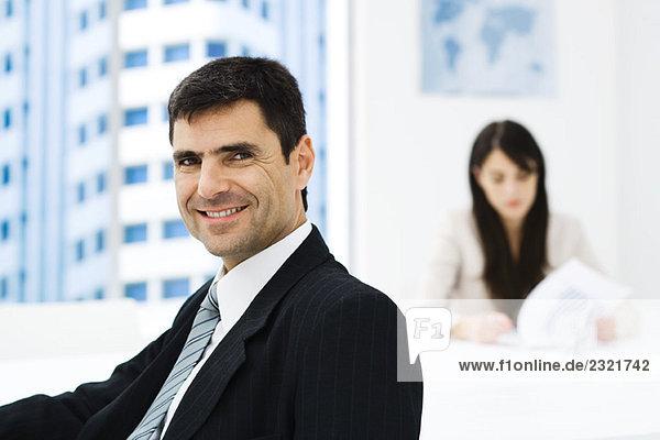 Geschäftsmann im Büro  lächelnd vor der Kamera  Porträt