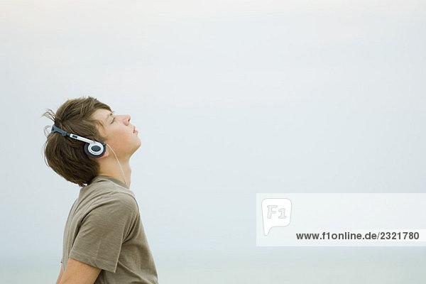 Teenage boy listening to headphones  looking up  side view