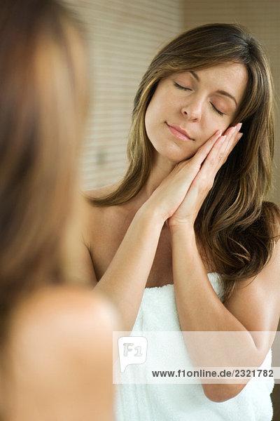 Frau vor dem Spiegel stehend mit geschlossenen Augen  Kopf auf umklammerten Händen ruhend  lächelnd