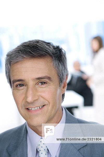Erwachsener Geschäftsmann  lächelnd vor der Kamera  Porträt