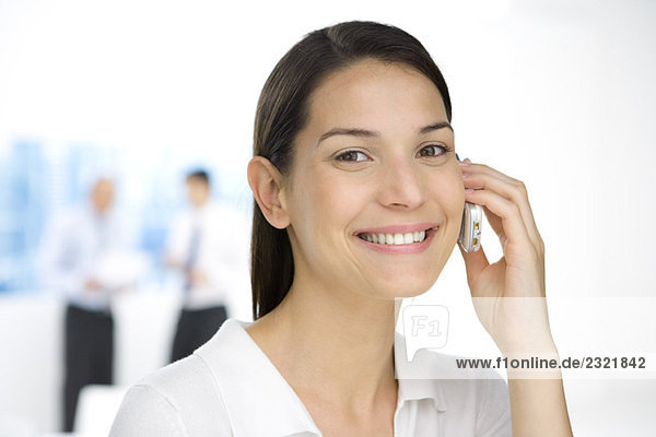 Junge Frau im Büro  mit dem Handy  lächelnd vor der Kamera  Porträt
