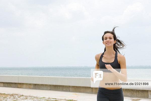 Junge Frau am Strand  Haar zerzaust  lächelnd