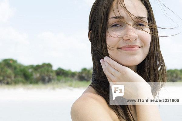 Junge Frau mit Haar zerzaust durch Wind  Lächeln in die Kamera  Nahaufnahme