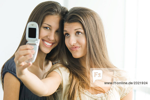 Teenage Zwillingsschwestern fotografieren selbst mit Handy  ein Lächeln in die Kamera
