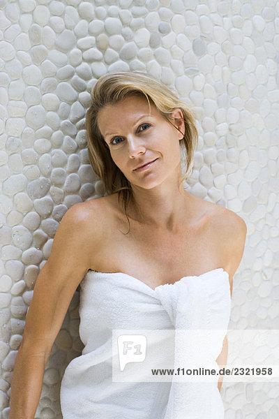 Frau umwickelt Handtuch  sich gegen Wand  lehnend lächelnd in die Kamera