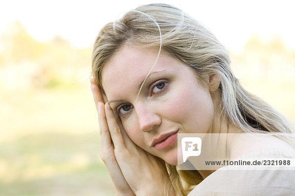 Frau an gelehnt verschränkt Hände  Blick in die Kamera