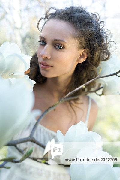 Junge Frau unter blühenden Baum Zweige  Lächeln in die Kamera
