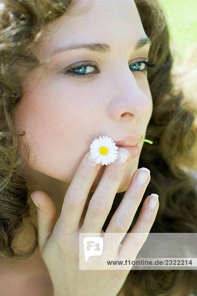 Junge Frau hält Flower in Mund  Wegsehen  Nahaufnahme