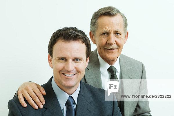Kaufmann mit Hand auf associate's Schulter  beide Lächeln in die Kamera  Portrait