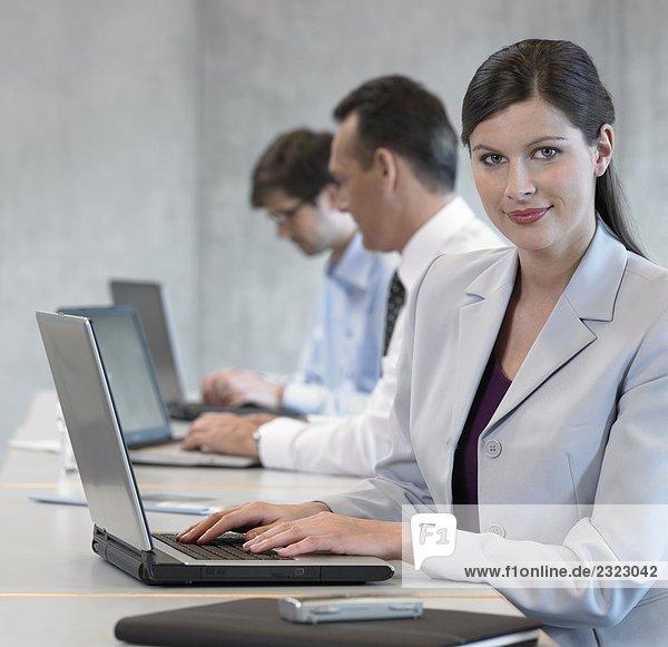 Porträt von geschäftsfrau mit Laptop und lächelnd mit ihren Kollegen sitzen im Hintergrund