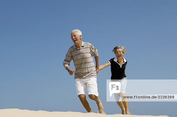 reifes Paar laufen hand in hand am Strand