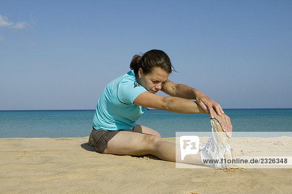 Young Frau macht stretching-Übungen am Strand