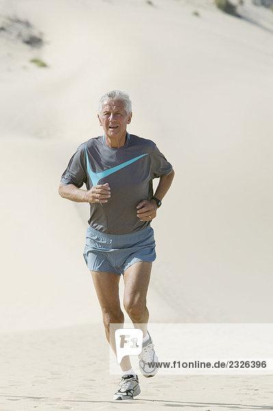 älterer Mann läuft auf sandigen Strand