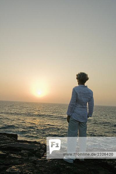 Rückansicht des reife Frau gerade Sonnenuntergang am Strand