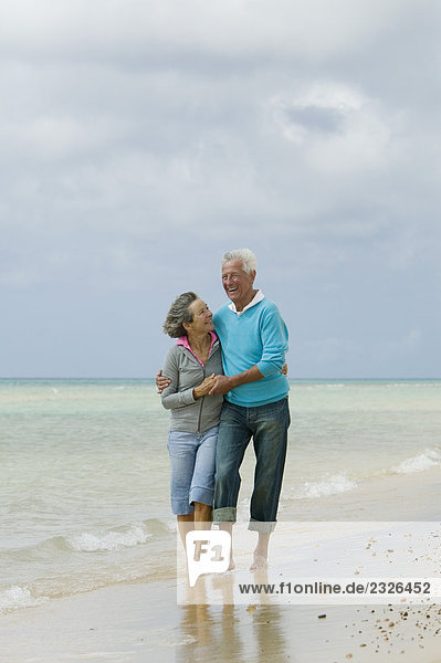happy mature couple embracing on beach