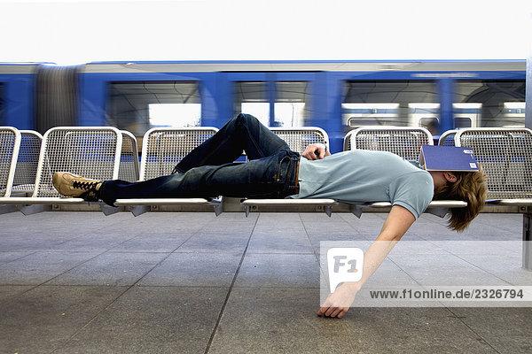 Teenager schlafen auf Bank am Bahnhof