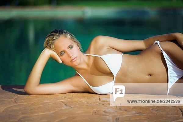 Junge Frau liegen am Pool Blick in die Kamera