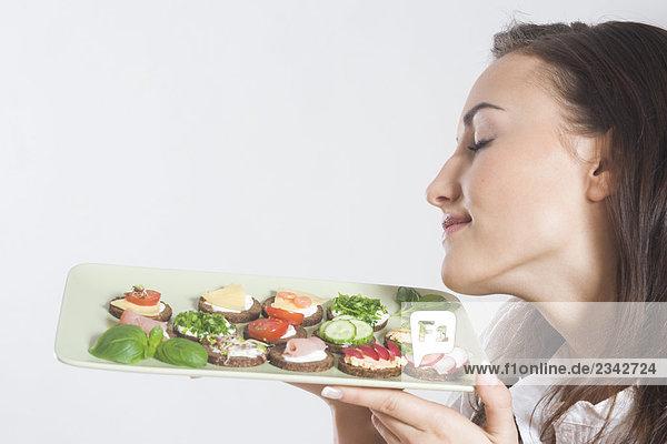 junge Frau hält Platte mit sandwiches