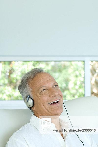 Erwachsener Mann hört Kopfhörer  lacht  schaut nach oben