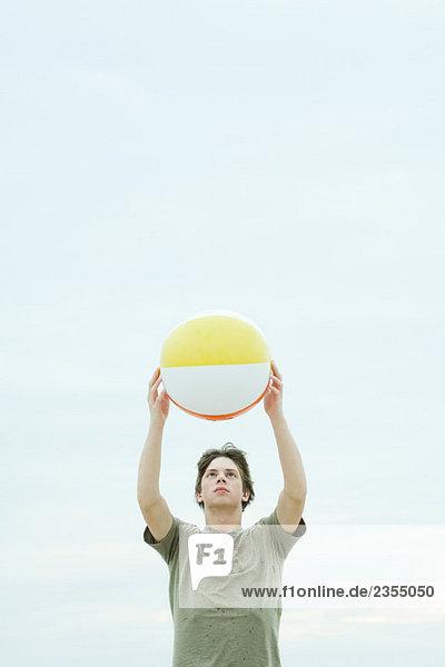 Teenage boy holding up beach ball  looking at camera