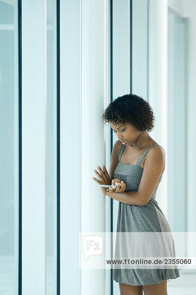 Junge Frau lehnt sich an die Stange und schaut auf das Handy.