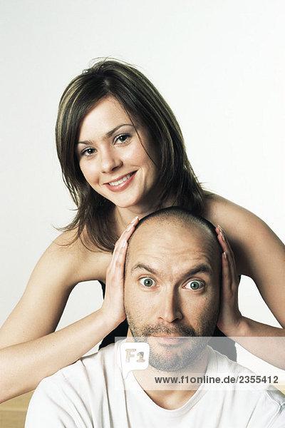 Frau bedeckt die Ohren des Mannes mit ihren Händen  lächelnd  beide sehen in die Kamera.