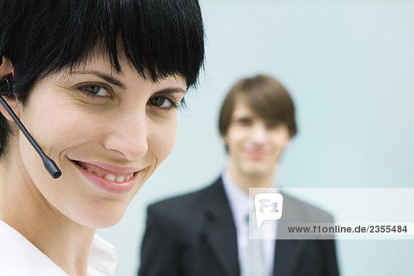 Frau mit Headset  lächelnd vor der Kamera  Geschäftsmann im Hintergrund