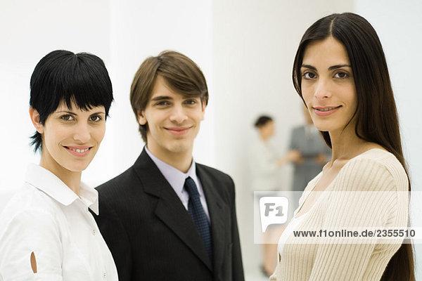 Drei junge Profis lächeln vor der Kamera  Nahaufnahme
