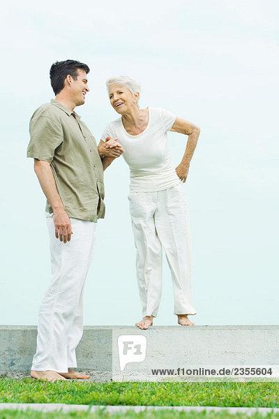 Seniorin auf niedriger Wand neben erwachsenem Sohn stehend  Händchen haltend  lächelnd