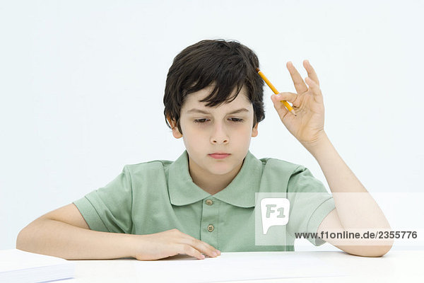 Boy sitting at table  holding pencil against head  looking down