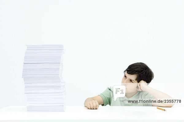 Boy sitting at table next to tall stack of homework  frowning