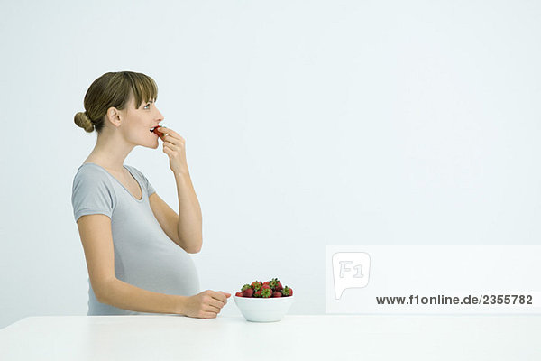 Pregnant woman eating bowl of strawberries  side view
